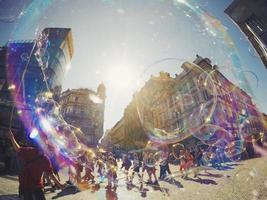 Prague, Czech Republic, 2020 - Group of people blowing bubbles in a city