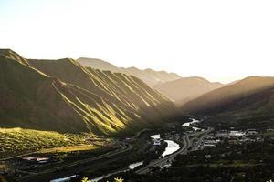 Stream running through a valley of green mountains