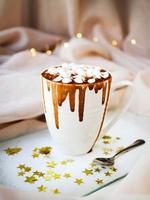 taza blanca con salsa de caramelo y malvaviscos