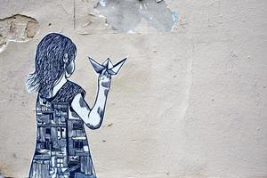 Montmartre, France, 2020 - Street art of a girl holding a paper boat