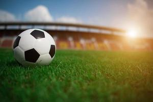 Soccer ball on grass with stadium background photo