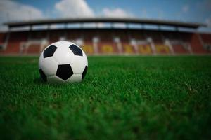 A soccer ball on grass with stadium background photo