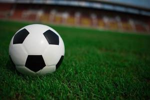 Balón de fútbol sobre césped con fondo de estadio foto