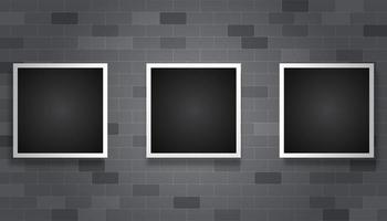 Marcos de cuadros oscuros colgando sobre fondo de ladrillo gris