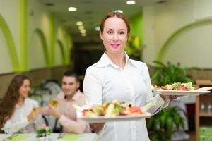 camarera sirviendo comida a los visitantes