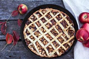 Homemade pie with apples on black wooden background