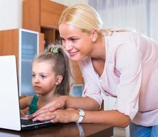 Woman and daughter chatting online photo