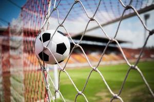 Soccer ball soars into goal net photo