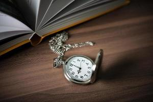 Close-up of a golden pocket watch and a book