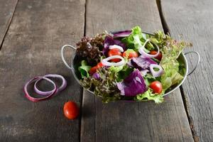 Fresh vegetable salad with rustic old wooden background photo