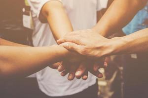 varias personas unen sus manos juntas
