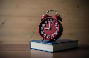 Alarm clock on wooden table with a book