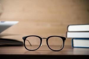 Glasses on a wooden table with books