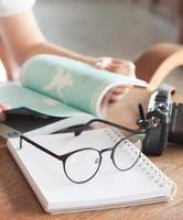 Woman reading a book with glasses and a camera on a table