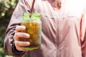 Mujer sosteniendo un frasco de vidrio con refresco