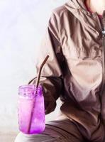 persona sosteniendo un vaso morado mientras está sentado