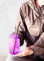 persona sosteniendo un frasco de vidrio morado