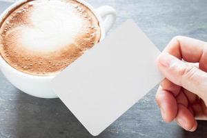 persona sosteniendo una tarjeta de visita en blanco con un café con leche foto