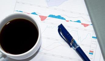 Top view of a pen and coffee on charts