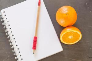 Red pencil on a notebook with oranges