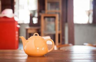 Teapot on a wooden table photo