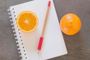 Red pencil and oranges with a notebook