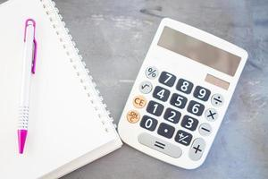 Calculator and notepad on a grey background