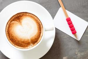 Top view of a latte with a name card and a pencil
