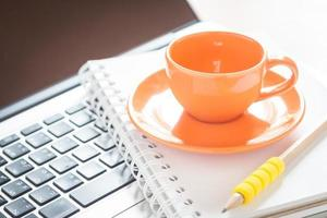 Coffee cup on a notebook on a laptop
