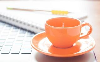 Laptop with a coffee cup and a notepad on a desk