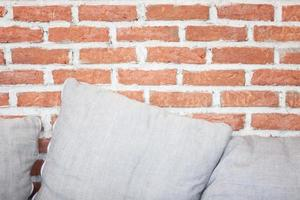almohadas grises contra una pared de ladrillos