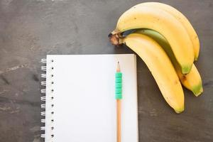 Top view of a notebook and bananas