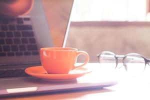 Orange coffee cup on a laptop with glasses photo