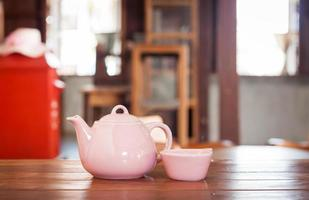 Teapot and cup on a wooden table photo