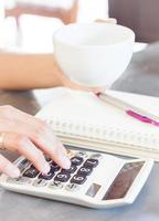 persona tomando café y usando una calculadora foto