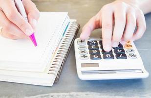 Primer plano de una persona que usa una calculadora y escribe en un cuaderno foto