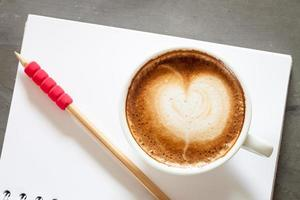 Top view of a latte with a pencil on a notebook