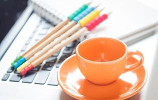 Coffee cup and pencils on a laptop