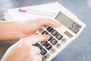 manos sosteniendo y presionando botones en una calculadora foto