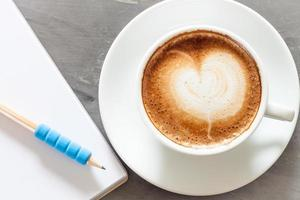 Coffee cup with a notepad and blue pencil on a grey background