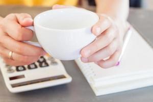 manos de mujer sosteniendo una taza de café con una calculadora foto