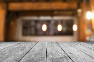 Mesa de madera blanca con una cafetería borrosa