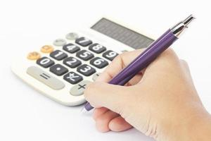 Calculator with hand holding a pen