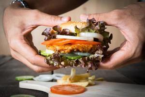 manos sostienen la hamburguesa sobre la tabla de cortar