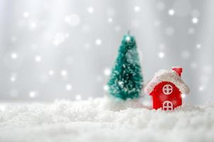 Miniature ed house and Christmas tree in the snow photo