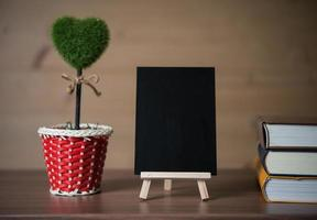 Small chalkboard with heart-shaped plant and books