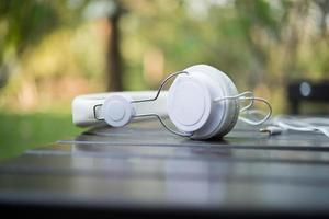 White headphones on wooden table with nature background