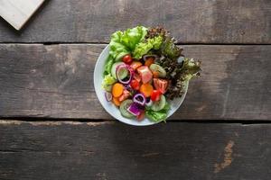 Fresh vegetable salad on wooden background
