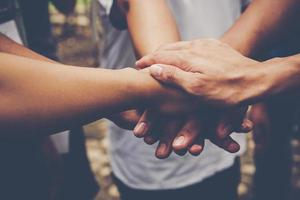 Several people join hands together