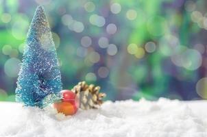 Árboles de Navidad en miniatura y adornos en la nieve.